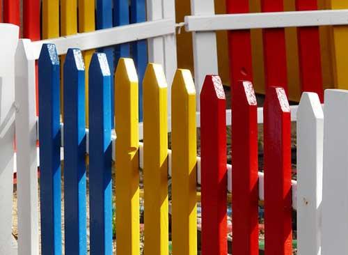 Fröhliche, bunte Gartenzäune aus Holz sind bei jungen Familien mit Kindern beliebt