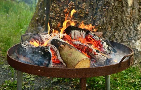 Eine Feuerschale mit einem Feuer aus Holzscheite versprüht pure Lagerfeuerromantik